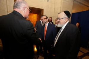 Leon Goldenberg, member of Agudath Israel of America's board of trustees warmly greets Cardinal Timothy Dolan in Albany as Rabbi Shmuel Lefkowitz, Agudath Israel's vice president for community affairs (R) and Yossi Menczer look on